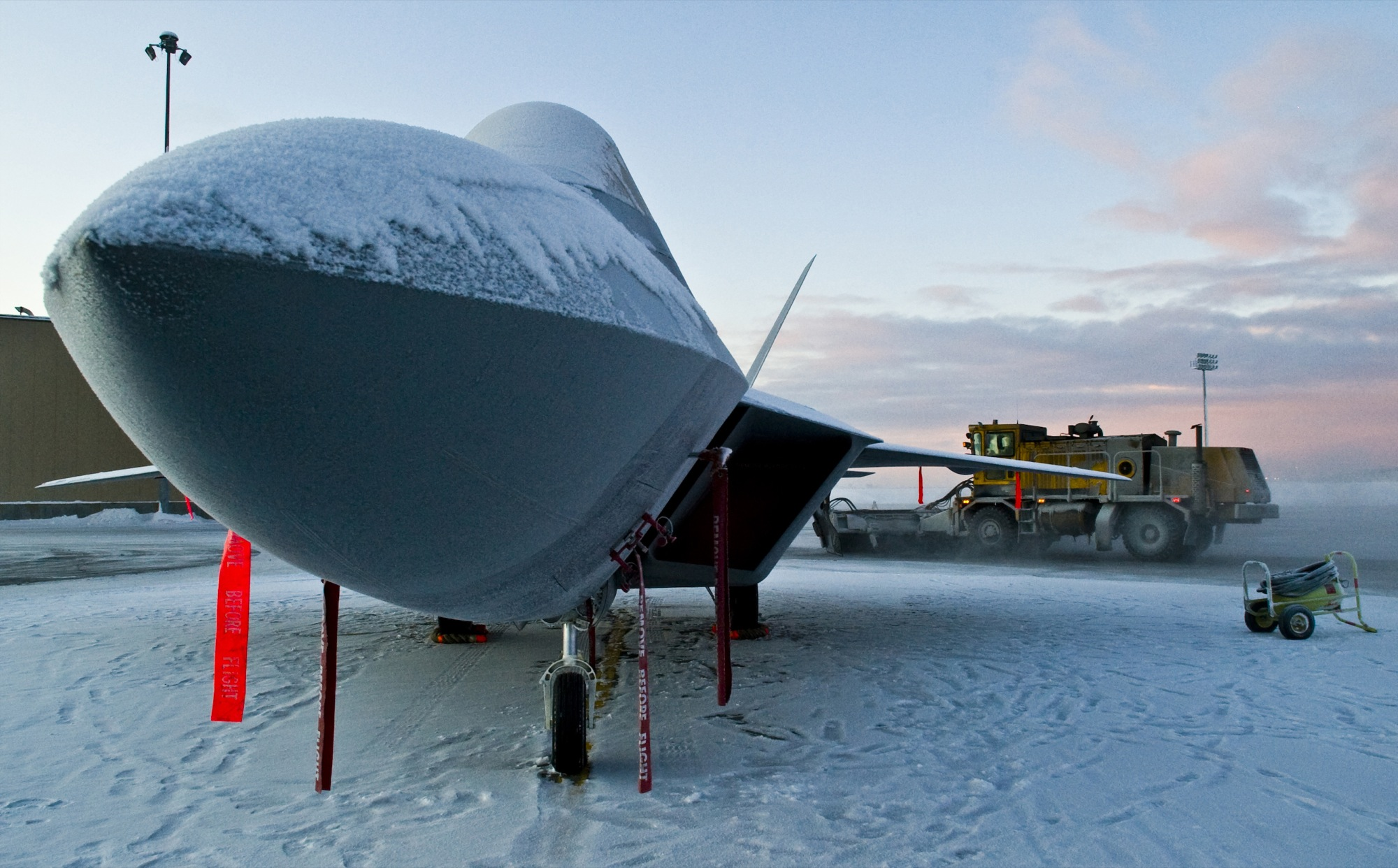 ELMENDORF AIR FORCE BASE, Alaska - A snow covered F-22A Raptor rests in a circle of snow as 3rd Civil Engineer Squadron Snow Removal members clear the runways Jan. 13, 2008. Elmendorf is the second operational base and the first in the Pacific Air Forces to have a permanent Raptor mission. (U.S. Air Force photo/Senior Airman Garrett Hothan)